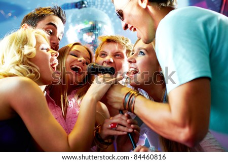 Portrait of joyous guys and girls singing at party in one microphone - stock photo