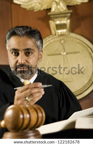 Portrait of judge sitting with book and pen in courtroom - stock photo