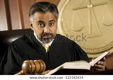 Portrait of judge sitting with book in courtroom - stock photo