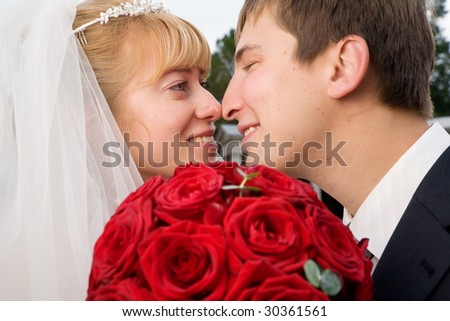 Portrait of just married kissing bride and groom with the wedding bouquet of beautiful red roses on the foreground
