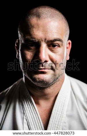 Portrait of karate fighter on black background