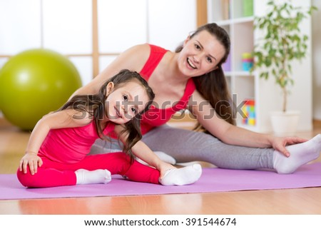 Portrait of kid and mother doing physical exercise at home - stock photo