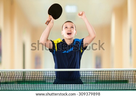Portrait Of Kid Playing Tennis celebrating flawless victory in table tennis  - stock photo