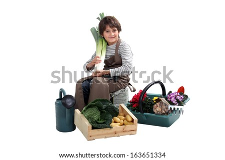 portrait of kid with vegetables and garden tools