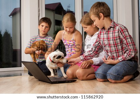 Portrait of kids playing with dogs at home - stock photo