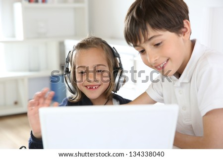 Portrait of kids waving at webcamera with laptop - stock photo