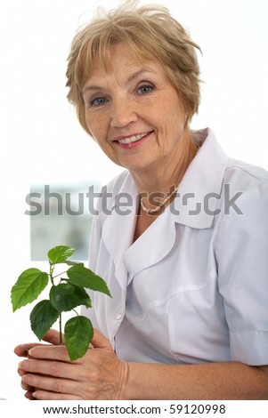 Portrait of kind and friendly woman with green plant - stock photo