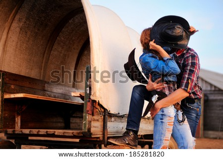 Portrait of kissing a guy and girl in cowboy hats - stock photo