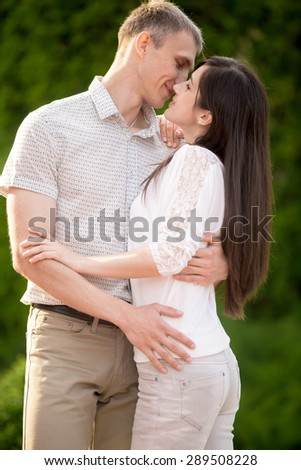 Portrait of kissing couple, young man and woman on date in park, embracing each other - stock photo