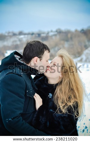 Portrait of kissing man and woman outdoors on a cold winter - stock photo