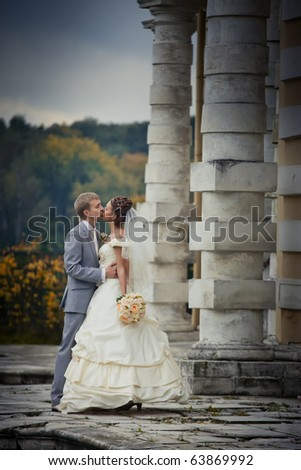 Portrait of kissing newlyweds in autumn park - stock photo