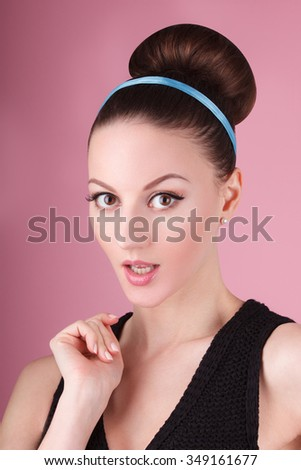 Portrait of lady with clean make-up and hair bun in the pink background in retro 60's style vintage