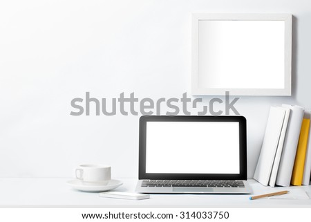 portrait of laptop with blank screen on working desk and blank frame on white wall with copy space - stock photo