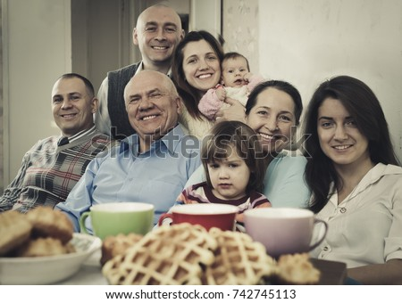 Portrait of large happy multigeneration family having tea at home