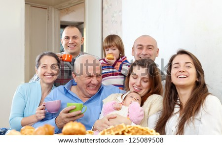 Portrait of large multigeneration family having tea at home  together - stock photo