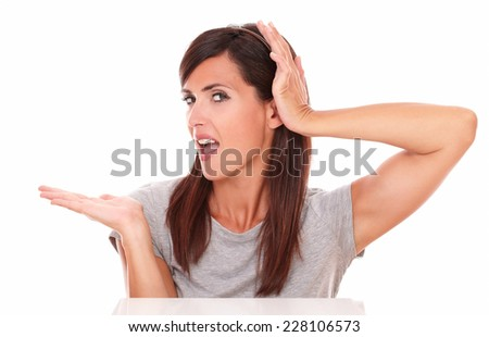 Portrait of latin woman holding her right palm up while screaming and touching her head on isolated white background - copyspace