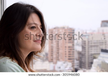 Portrait of latina middle aged woman looking through the window - stock photo