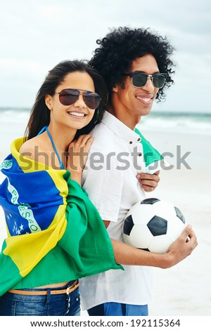 Portrait of latino couple with Brasil flag and soccer ball for world cup - stock photo