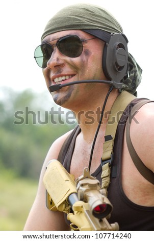Portrait of laughing armed Ukrainian national guard solider talk on headset radio.Dangerous military man with gun.Happy border patrol soldier protecting borders