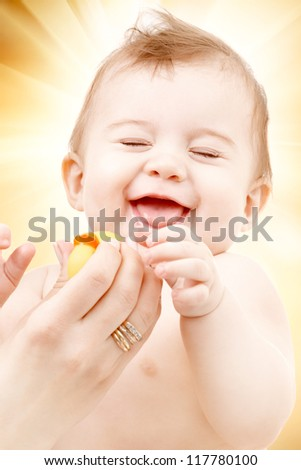 portrait of laughing baby boy in mother hands playing with rubber duck - stock photo