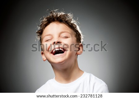 Portrait of laughing boy on gray background - stock photo