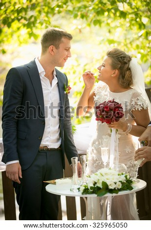 Portrait of laughing bride and groom looking at each other at wedding ceremony - stock photo