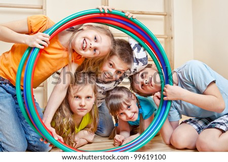 Portrait of laughing children looking through hula hoops - stock photo