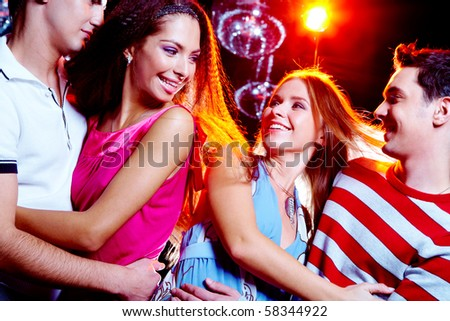 Portrait of laughing couples looking at each other at party