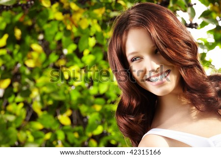 Portrait of laughing curly beauty in a summer garden - stock photo
