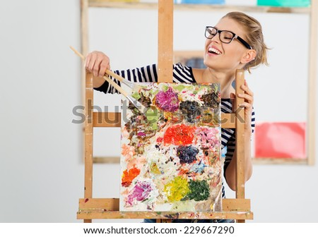 Portrait of laughing female painter showing her colorful artwork. Young lovely woman artist standing behind easel in her studio.  - stock photo