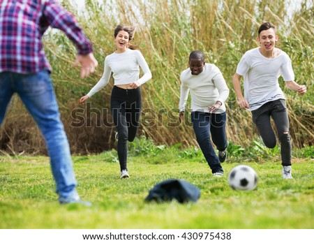 Portrait of  laughing four friends posing on countryside field with ball in sunny day