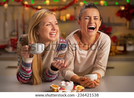 Portrait of laughing girlfriends having christmas snacks in christmas decorated kitchen - stock photo