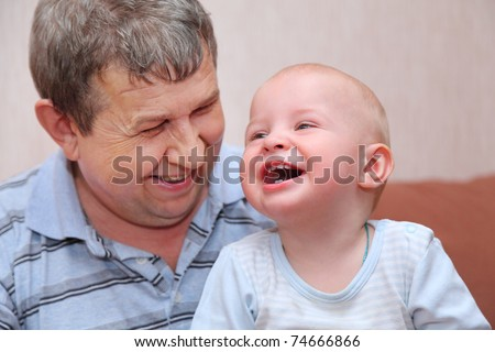 Portrait of laughing, happy old man and his grandson, focus on little baby tooth - stock photo