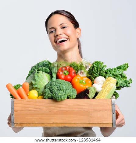 Portrait of laughing happy young woman holding a crate full of fresh organic produce on grey background, promoting healthy living, diet and lifestyle - stock photo