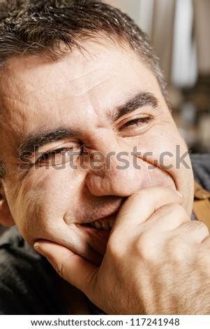 Portrait of laughing man closing mouth with hand - stock photo