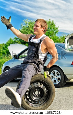 Portrait of laughing mechanic sitting on a tire on a road.