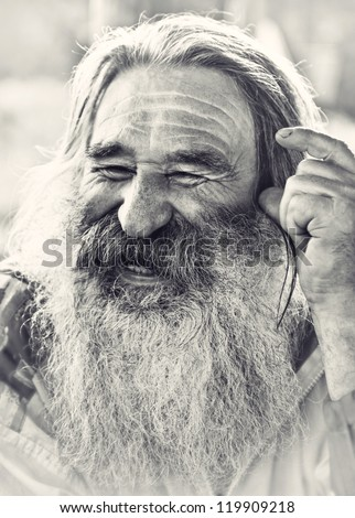 portrait of  laughing old man with gray beard - stock photo