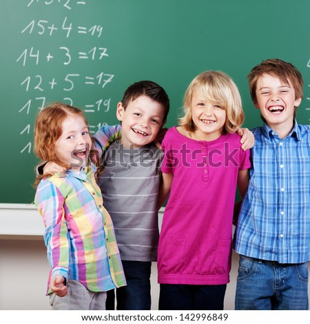 Portrait of laughing schoolchildren in front of panel