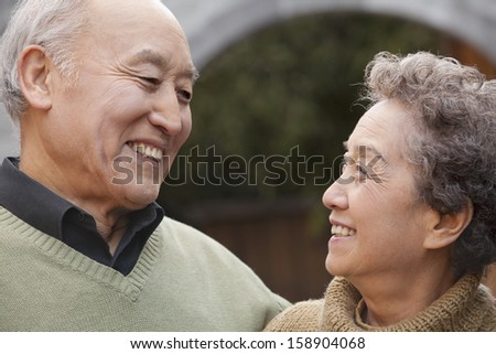 Portrait of laughing senior couple in front of round arch