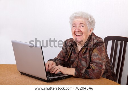 Portrait of laughing senior woman working at computer - stock photo