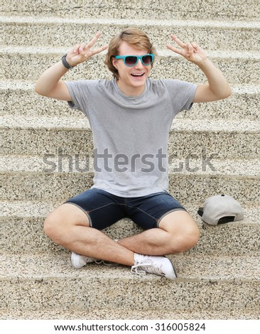 Portrait of laughing teenage boy showing victory symbol at the camera. - stock photo