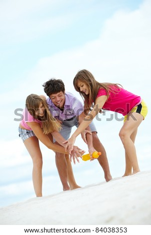 Portrait of laughing teenagers having fun on sandy beach