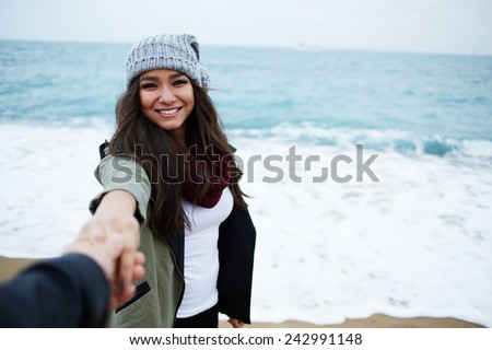 Portrait of laughing woman in love with hand held by her boyfriend standing against the ocean - stock photo