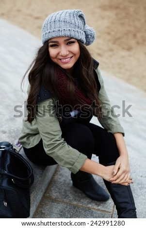 Portrait of laughing woman sitting on the steps at leisure time outdoors - stock photo