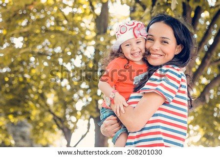 Portrait of laughing young beautiful mother and daughter  - stock photo