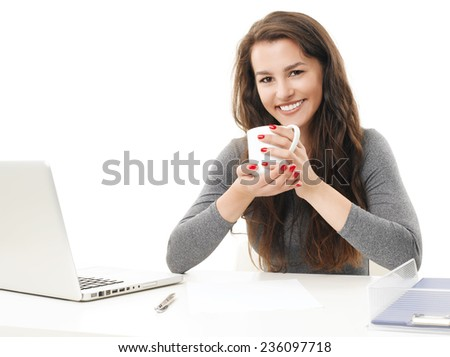 Portrait of laughing young business woman with laptop sitting at desk and drinking tea. Isolated on white background.  - stock photo