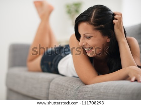 Portrait of laughing young woman laying on couch