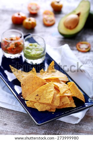 portrait of light and crispy corn chips served with salsa and guacamole at blue plate - stock photo