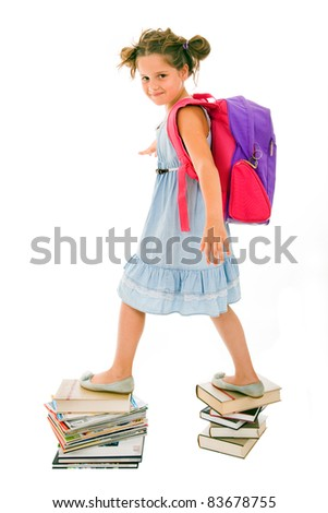 Portrait of litle girl with backpack walking from top to top of book piles - stock photo