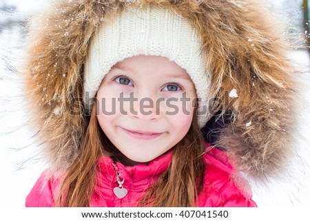 Portrait of little adorable girl in snow sunny winter day - stock photo